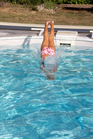 young  woman plunge into the pool at home Standard-Bild
