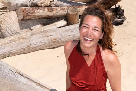 middle aged cheerful woman having fun on the beach laughing happiness