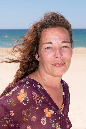 beautiful woman middle aged brunette closeup portrait in sand sea beach
