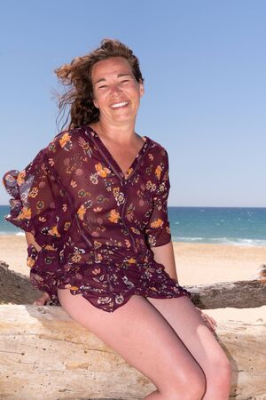 curly brunette happy woman enjoying freedom laughing on sea beach Stock fotó