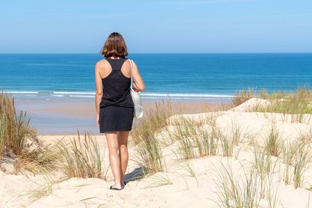 young woman from behind walking in sand dunes of Atlantic ocean in cap ferret France