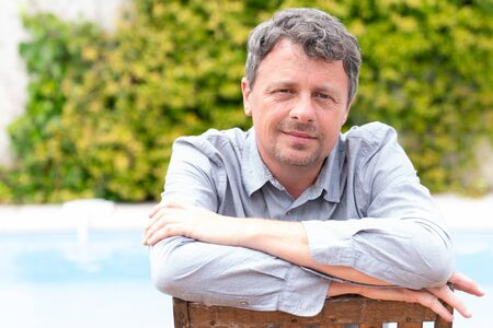 Portrait of middle aged man caucasian smiling and looking at camera outside at home house garden pool background