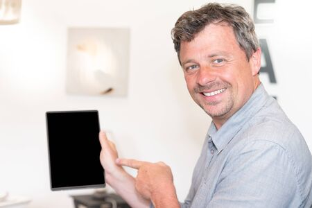 handsome man surfing using his tablet at home