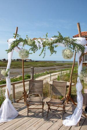 outdoor wedding reception with arch on the shore of sea in arcachon bassin in france