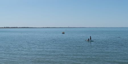 panorama young girls on stand up paddle board sap in water sea beach summer season boat and ship vacation concept Zdjęcie Seryjne
