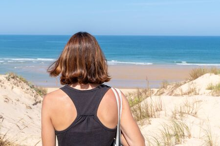back view behind brunette woman in sand dunes beach access of Lacanau atlantic ocean in France
