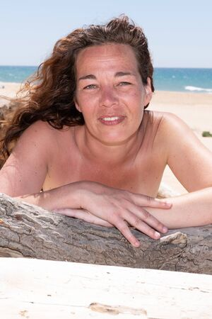 portrait of a forty woman on sand sea in swimsuit behind driftwood on beach of Lacanau France