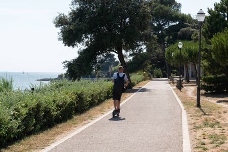 man on a scooter on the bike path in La Rochelle Charente, France