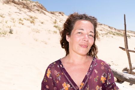 Portrait of mature woman resting on the nature dunes sand beach smile happy Stock Photo
