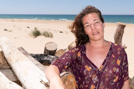 woman sitting on the beach in sand with copy space