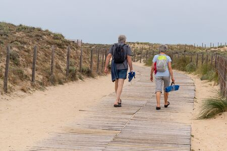 man and woman retired couple walking on the wooden path at the beach