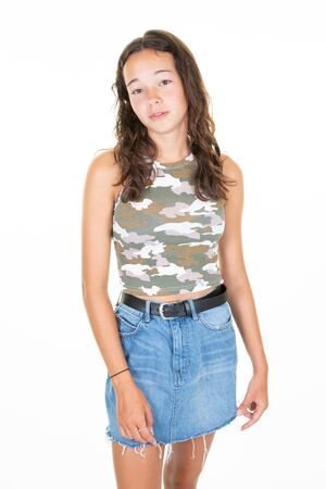 Young beautiful woman wearing denim skirt camouflage t shirt over isolated white background