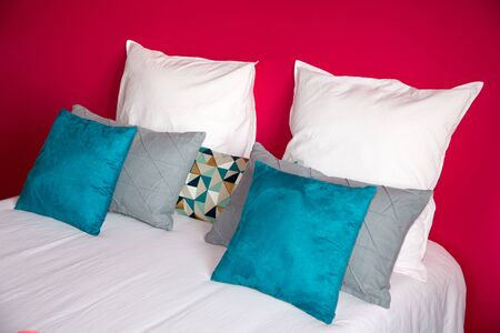 Different pillows on bed in room interior decor