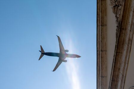 airplane flying over french city building in sunny day