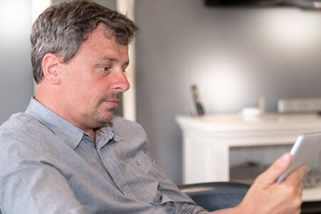handsome middle aged man using tablet at home grey wall