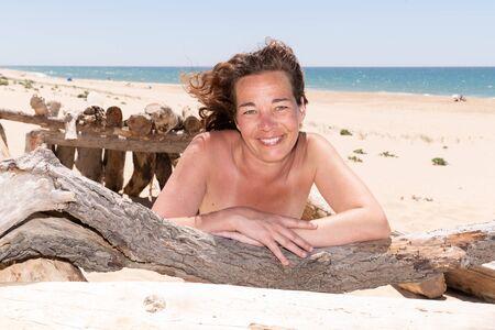 Porträt der lächelnden brünetten Frau, die auf Treibholzstrand liegt? Standard-Bild