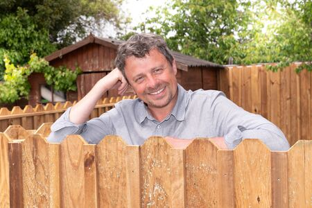 handsome middle aged man leaning on wall wood outside the house