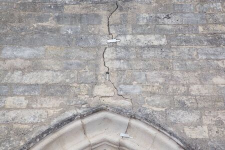 Rulers measuring the cracks in church wall