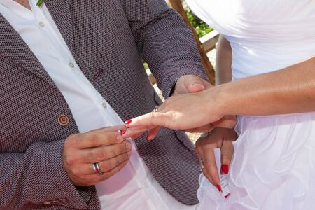 Wedding groom wears bride ring exchange Stock Photo