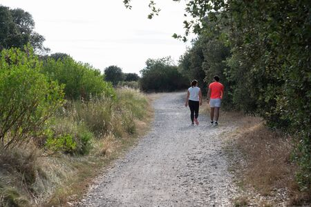 couple go to beach of isle Noirmoutier by sand pathway in Vendee France