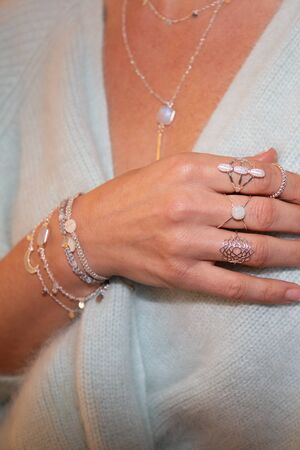 cropped view of the young woman with a silver necklace  bracelets and rings