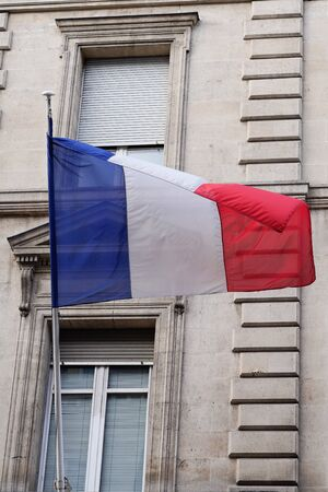 French flag waving in front of the facade of city hall france