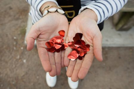 Festive red heart glitter confetti in hands of girl top view