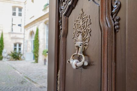 open entrance wood door knocker in beautiful city center French luxury house Bordeaux