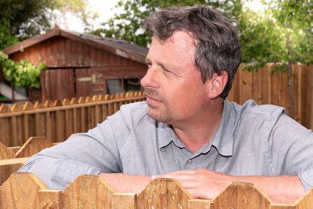 Profile portrait closeup of stylish bearded man 40s in grey blue shirt looking side in green wood garden park Stok Fotoğraf