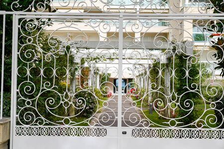 white metal driveway entrance gates set building in brick fence