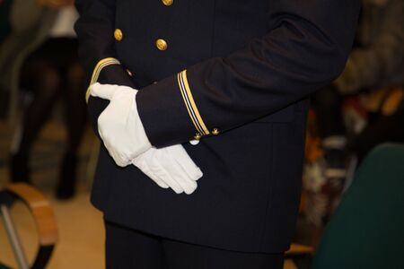 Hands of officer army in white gloves during official event