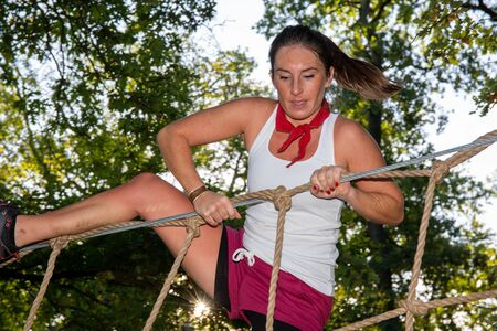 pretty sporty woman in obstacle Course rope ladder in Outdoor Boot Camp Фото со стока