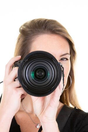 Portrait Of woman pretty Photographer With Camera Against White Studio Wall 免版税图像