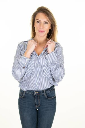 Smiling blonde haired dressed in blue blouse and jeans trousers stands on wall white background Banque d'images