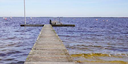 Muelle de madera en la orilla de un gran lago de Maubuisson Carcans France Foto de archivo