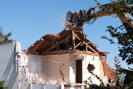 excavator in demolition of home residential building