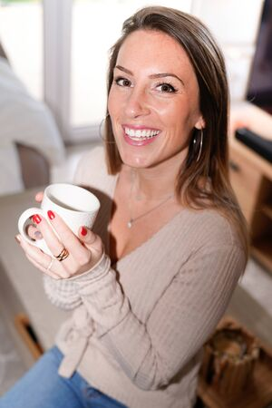Happy woman holding tea mug coffee cup in winter at home Banque d'images - 138272451