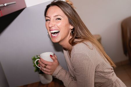 Young happy laughing woman drinking coffee on the kitchen in the morning Banque d'images - 138274677