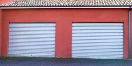 red industrial building facade closed two grey roller shutter gate