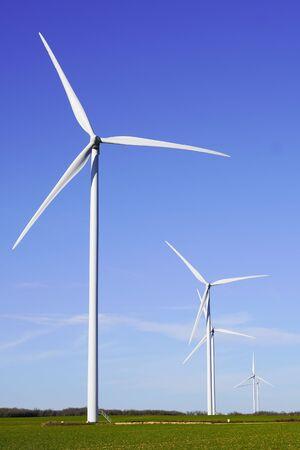 Flying windwheels wind power above big wind turbine on field in sunny day