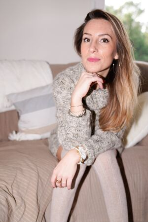 amazing young woman sitting house sofa free time at home wear casual pullover clothes indoors