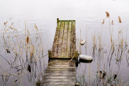 Wooden jetty in the wild lake water winter day