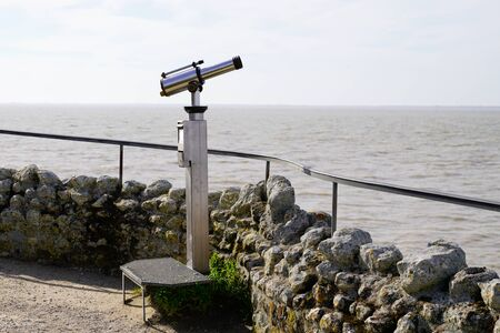 Touristic vintage paid telescope in sea coast horizon