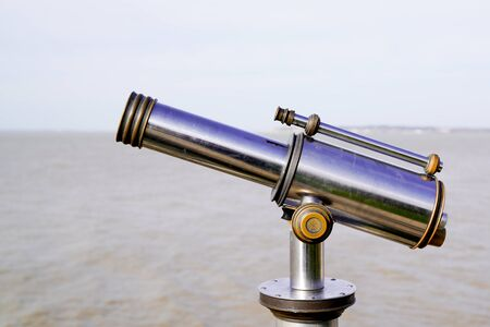 Touristic old seaside pay to view silver paid telescope in sea coast horizon