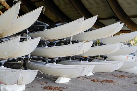 hulls of school sailboats racked one above another on two levels in a dry rack boat storage facility in winter season