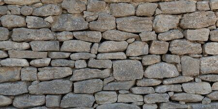 Old Grey stone wall made of large gray small rectangular hewn natural stones Stok Fotoğraf
