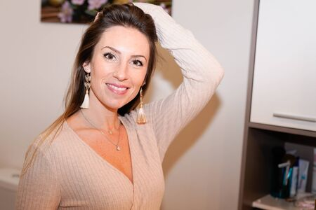 beautiful happy brunette woman at home hand on hairs Standard-Bild - 143296316