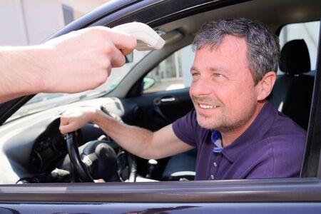 poste de contrôle du coronavirus sur la voiture de rue homme médecins vérifiant la température corporelle épidémie de virus corona covid-19