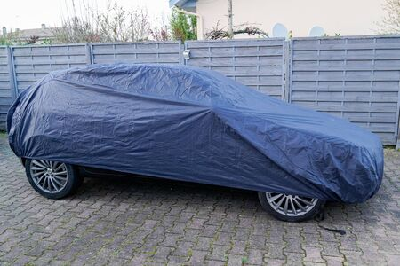 sport luxury car parked under blue colored protective cover jacket outside