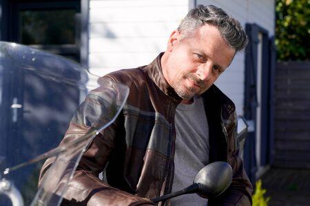 handsome beard man in brown motorbike fashion jacket sit on motorcycle outdoors